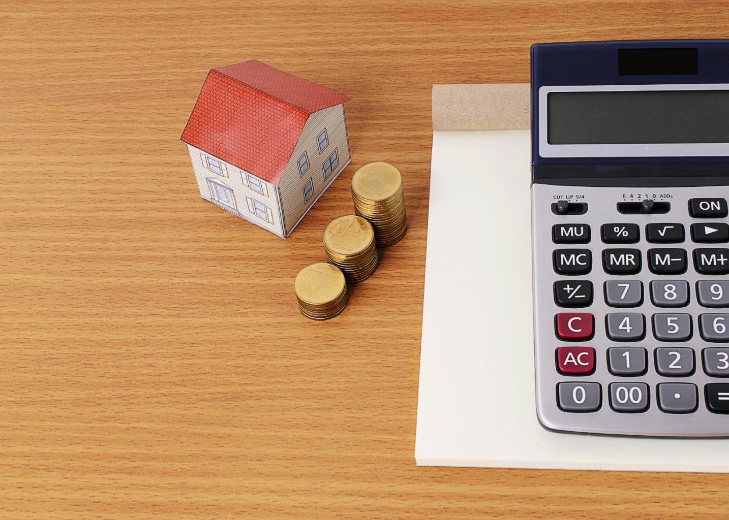 Calculator with notepad and paper house with coins stack