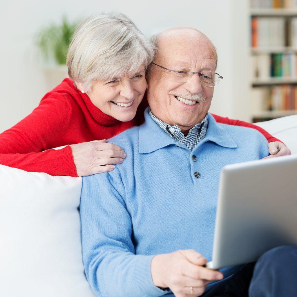 Happy elderly couple looking at laptop
