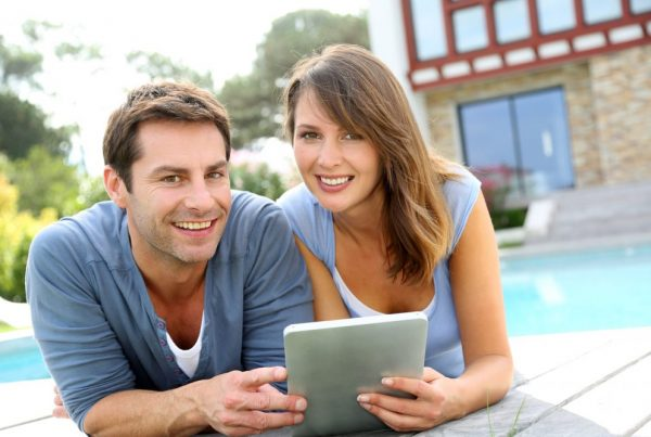 happy couple with tablet outside home